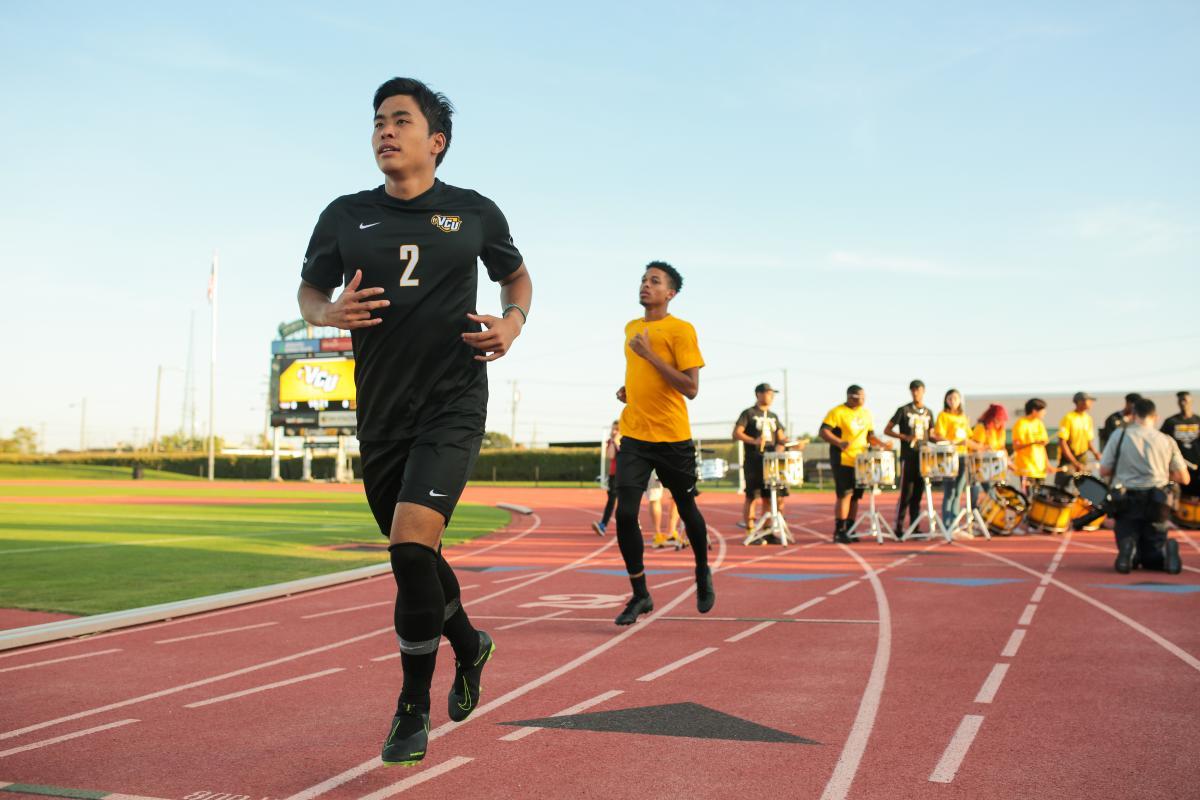 Senior defender Ryo Shimazaki runs onto the field from the locker room before the match. Photo by Jon Mirador